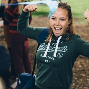 Lachende jongedame die haar spierballen toont op Questtrek, een programma voor echte persoonlijke ontwikkeling in het onderwijs.
