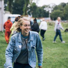 Lachende jongedame op een grasveld met leeftijdsgenoten.