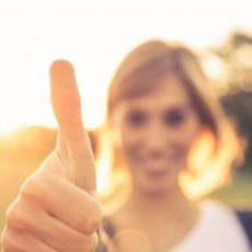Lachende vrouw die haar duim naar de camera opsteekt.